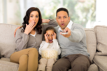 scary girl: family watching scary movies at home