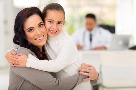 madre trabajando: madre e hija hermosa abrazos en el consultorio médico