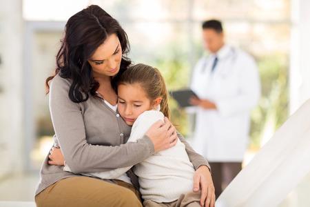 ragazza malata: triste giovane donna e sua figlia malata in attesa di controllo nella stanza del medico