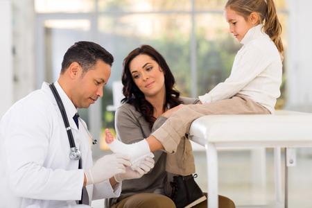 pies masculinos: vendaje del pediatra que cuida tobillo poco del paciente