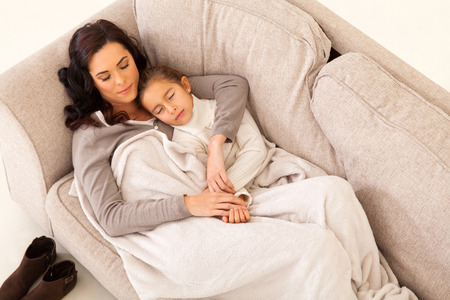 cute mother and her little girl sleeping on the couch photo