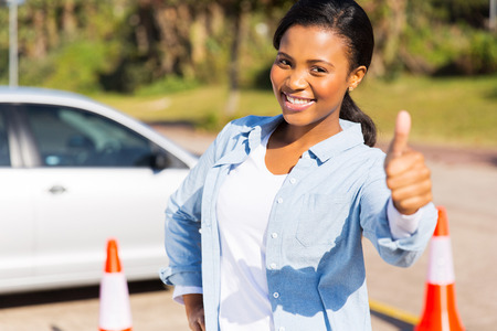 driving school: happy young african girl standing in driving school giving thumb up