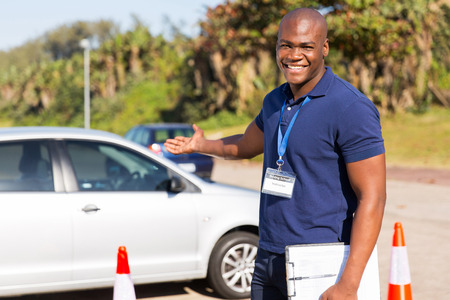 cheerful young african driving instructor presenting a car Stock Photo
