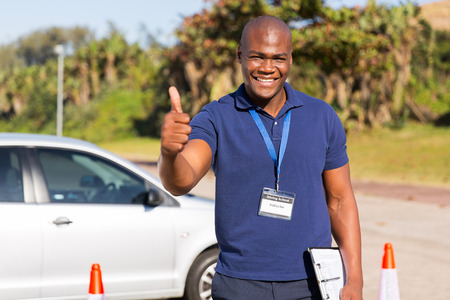 man's thumb: portrait of handsome african driving school instructor giving thumb up