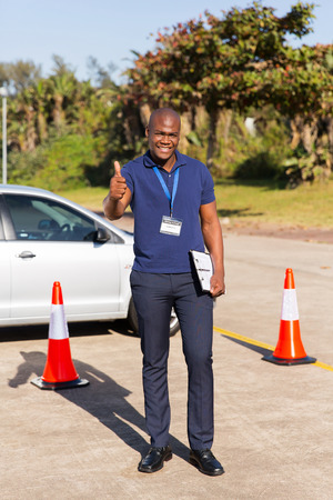 driving school: happy driving instructor in testing ground giving thumb up