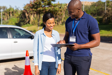 on the job training: african learner driver with instructor before talking driving test