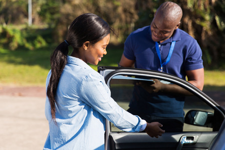 happy female african learner driver with instructor doing pre driving inspection photo