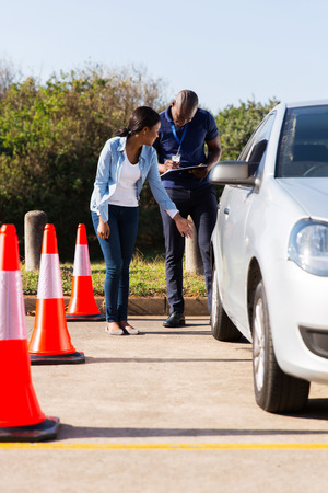 driving school: african student driver and male instructor pre test inspection