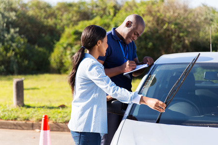 windscreen wiper: female african learner driver checking windscreen wiper during a driving test Stock Photo