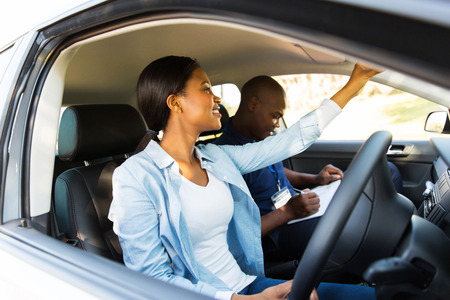 learner: african learner driver adjusting rear view mirror before a driving test