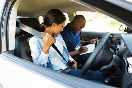 cinturon seguridad: joven muchacha africana de ponerse el cinturón de seguridad durante una prueba de conducción Foto de archivo