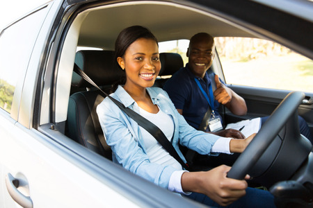 man's thumb: happy young african woman taking driving lessons from instructor