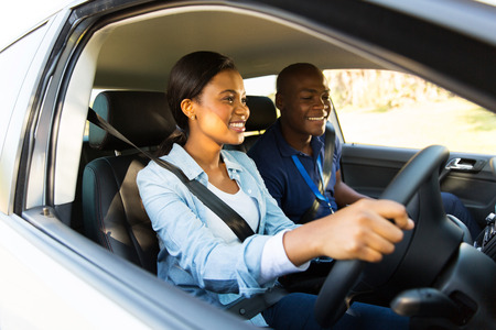examiner: happy african learner driver taking lessons from instructor Stock Photo