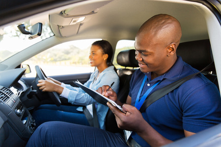 african girl taking driving test with professional instructor