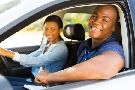 happy male african american driving instructor and student driver during lesson