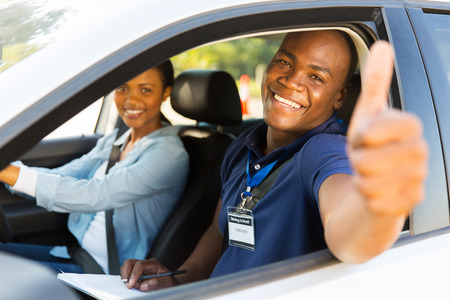 man's thumb: happy male african driving instructor in a car with learner driver giving thumb up Stock Photo