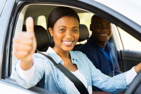 cinturon seguridad: conductor africano hembra hermosa estudiante con el instructor que da el pulgar para arriba