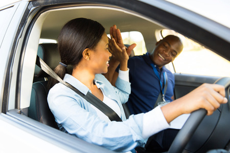 learner: cheerful young african learner driver and driving instructor high five