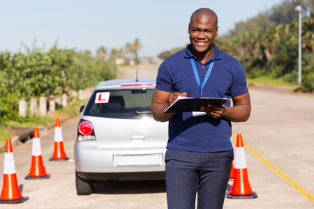 driving school: portrait of african american driving instructor writing on clipboard Stock Photo