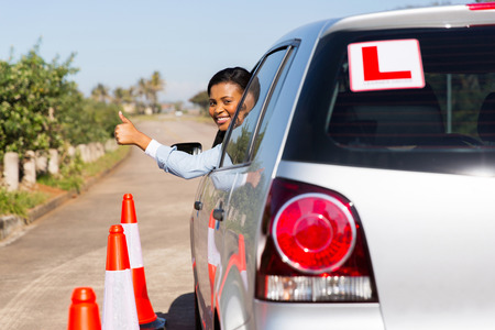learner: beautiful african learner driver looking out of the car window and giving thumb up