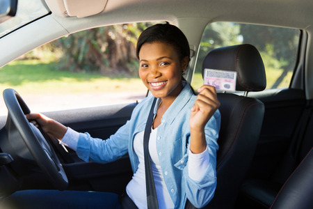 pretty african woman in a car showing her drivers license photo