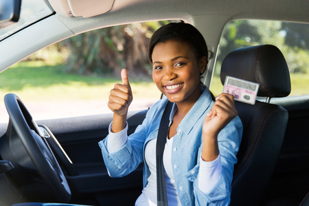 cheerful african girl holding her driver's license she just got
