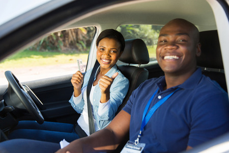 passed test: african woman has passed her driving test, holding drivers license Stock Photo