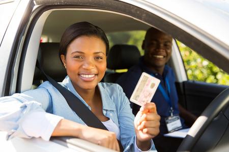 cinturon seguridad: conductor del estudiante africano pasa la prueba de conducción y la celebración de su licencia de conducir