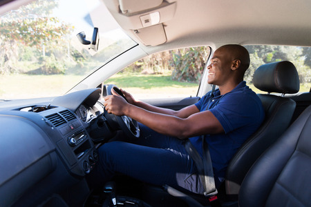 new motor car: happy young african american man driving a car