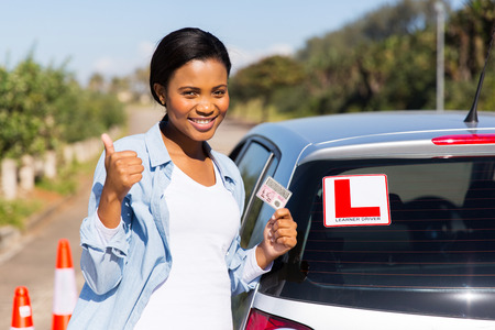 cheerful black woman showing a driving license she just got photo