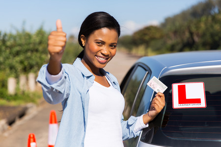 learner: attractive african learner driver holding her drivers license Stock Photo