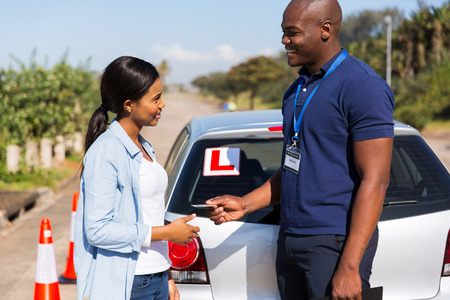 friendly african driving instructor handing driving license to student driver