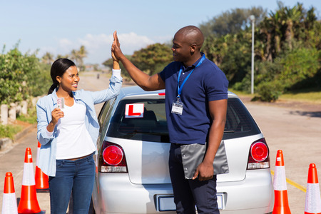 instructors: happy african girl and driving instructor doing high five after getting her driving license