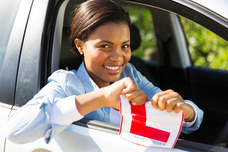 learner: african girl sitting in a car tearing a L sign after having her drivers license Stock Photo
