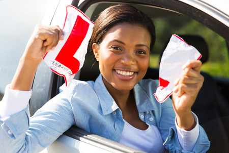 learner: happy african female driver tearing up her L sign sitting in a car