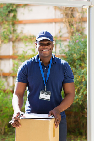 on box: handsome african american delivery man with a parcel standing at the door