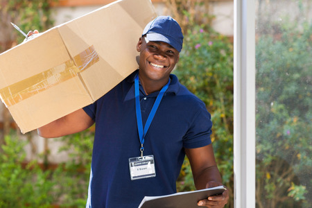cheerful african courier standing with parcel at the door