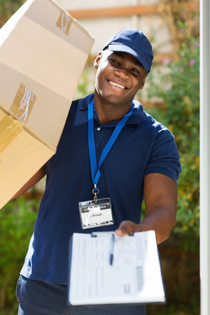 delivery service: african delivery man carrying parcel and presenting receiving form