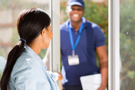 african woman opening door for courier delivery guy Stock Photo