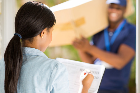 courier: rear view african woman signing receiving paper from courier guy