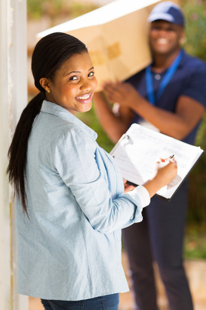pretty black woman signing document for receiving package photo
