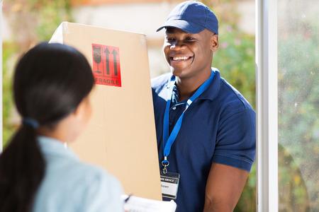 azul marino: amigable joven repartidor de afroamericano entrega de un paquete