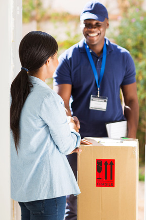 packages: friendly african delivery man handshaking with customer