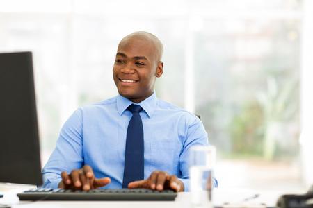 personas mirando: apuesto hombre de negocios africano que mira la pantalla del ordenador