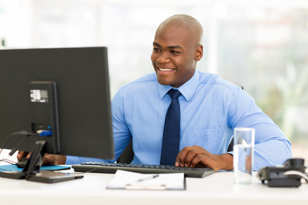 young man smiling: happy afro american business man using computer