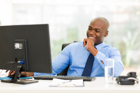 white people: happy young african businessman working on computer
