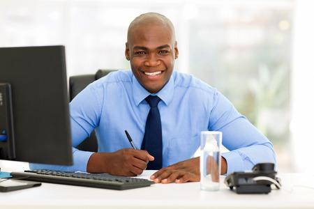 persona escribiendo: feliz trabajador corporativo africano que trabaja en oficina Foto de archivo