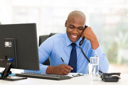 business success: happy african businessman talking on landline phone and writing report
