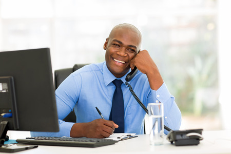 phone professional: cheerful african american businessman talking on phone in the office
