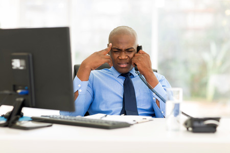 confused african business man talking on telephone in office